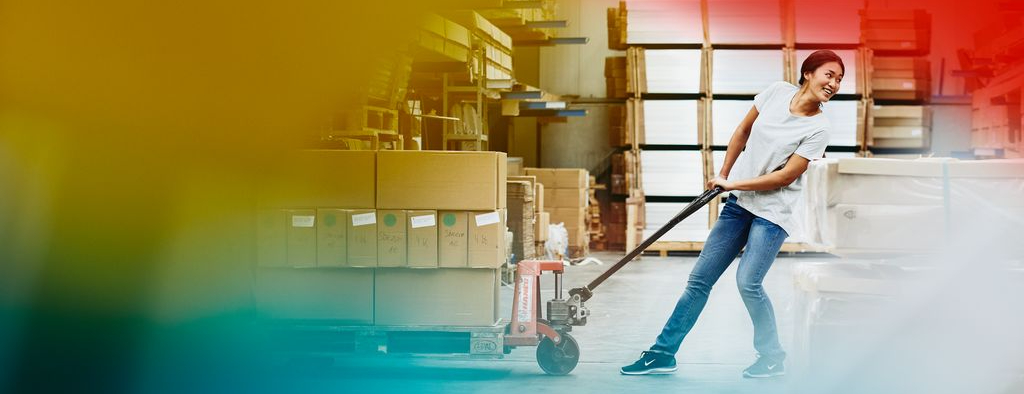 Female blue-collar worker operating a pallet loader. Primary colors yellow and red.